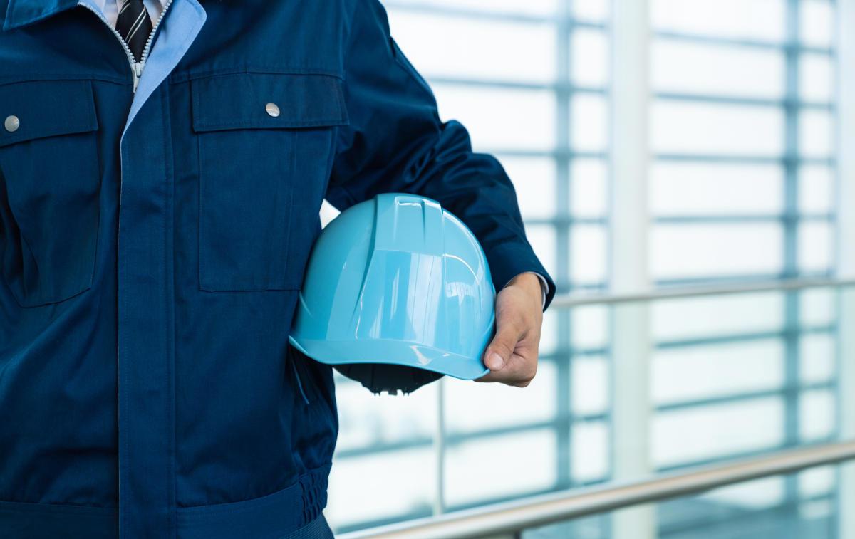 ヘルメットを持つ作業員